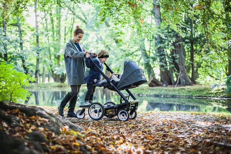 starsze dziecko jadące na dostawce do wózka Igo Urban Nomad podczas magicznego spaceru po przepięknym zielonym parku