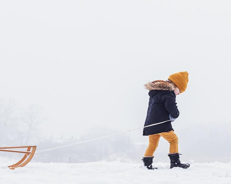 mały chłopiec spaceruje po śniegu ciągnąc za sobą sanki