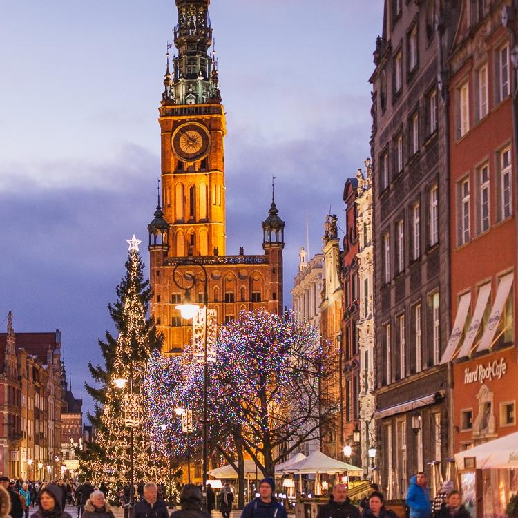 tłum turystów spaceruje po Długim Targu w Gdańsku podziwiając rozświetloną choinkę oraz pięknie podświetlony ratusz Głównego Miasta
