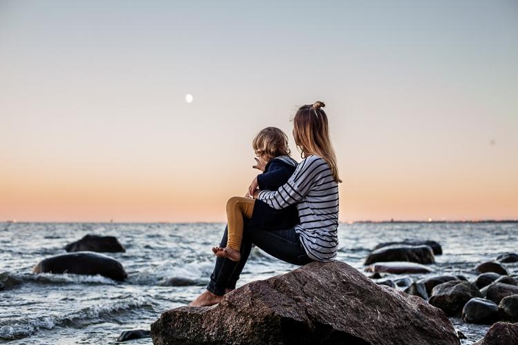 mama z synkiem siedzą nad morzem i oglądają zachód słońca