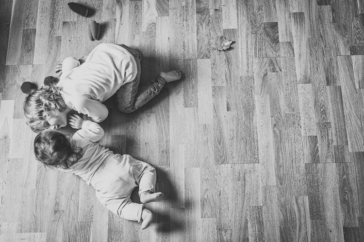 starszy brat przytula malutką siostrzyczkę na drewnianej podłodze mieszkania