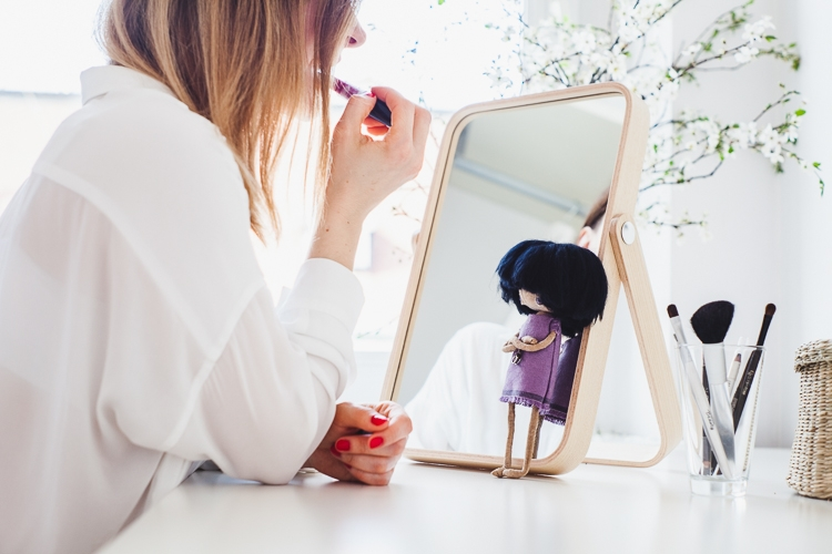 mała lalka totootse przygląda się jak dziewczyna maluje sobie usta