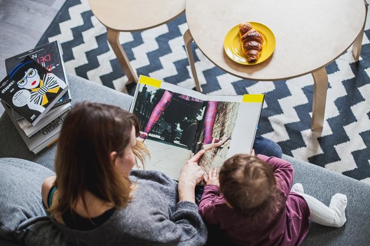 córka z mamą oglądają album fotograficzny siedząc na kanapie