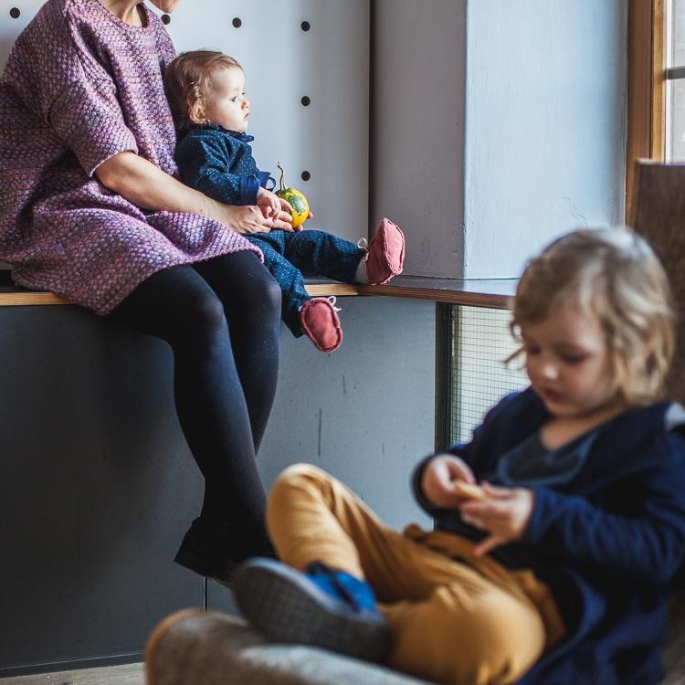 chłopiec w spodniach i marynarce mon chou siedzi na fotelu w kawiarni