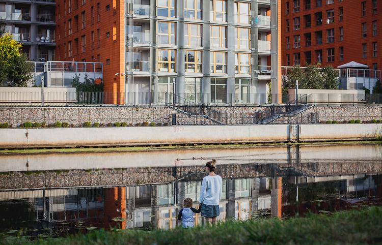 Widok na rzekę Motławę w której odbijają się nowe kamienice Wyspy Spichrzów w Gdańsku