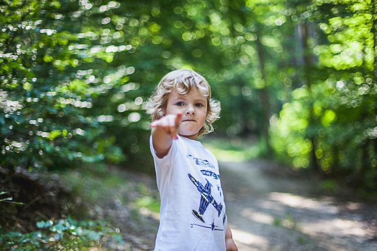 chłopiec pokazuje palcem las
