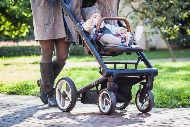 mom walking in the park with her little daughter in city stroller