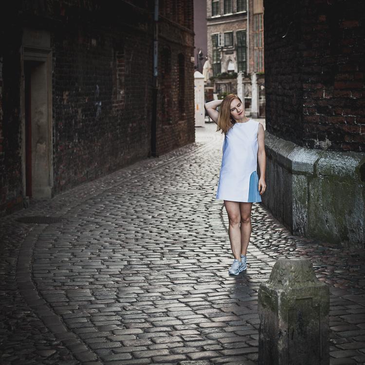 dziewczyna spaceruje po brukowanej ulicy Mariackiej w gdańsku