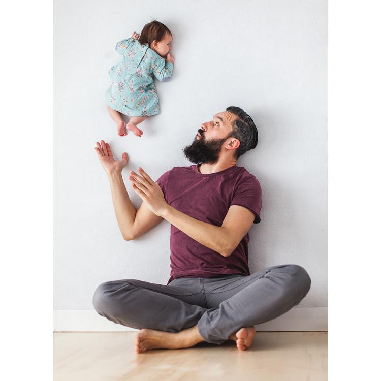 dad playing with newborn daughter
