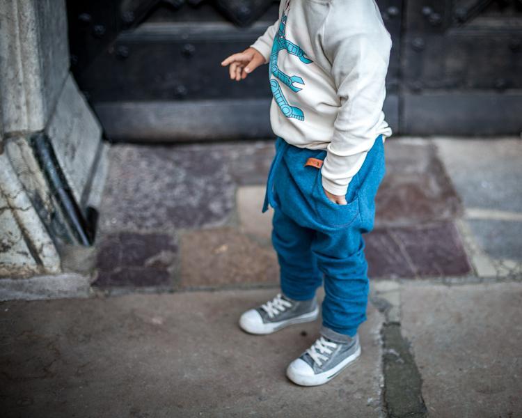 chłopiec w spodniach zezuzulla bawi się na ulicy w Gdańsku
