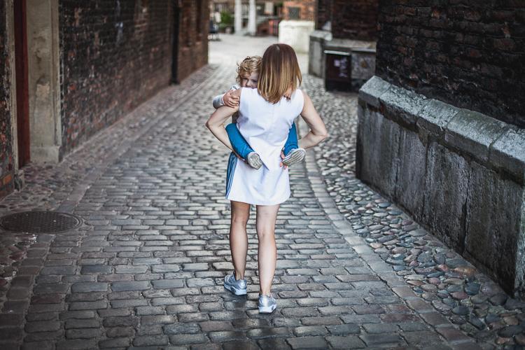 mama w białej sukience niesie syna po brukowanej ulicy
