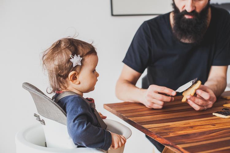 dziewczynka siedzi na krześle stokke steps a brodaty tata ozdabia pierniczki