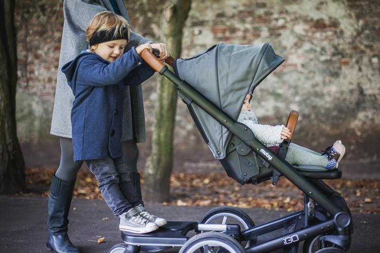 family walking in park with a Mutsy Igo stroller