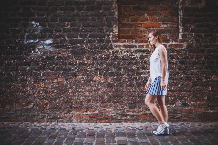 dziewczyna w białej sukience spaceruje po brukowanych uliczkach Starego Miasta w Gdańsku
