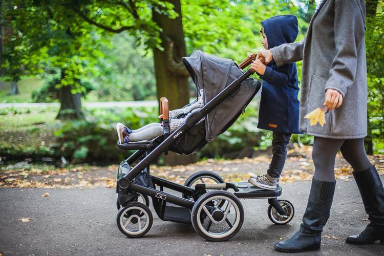 older son walking on a platform for Igo stroller