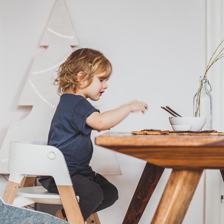 dzieci siedzą na krzesełku stokke steps