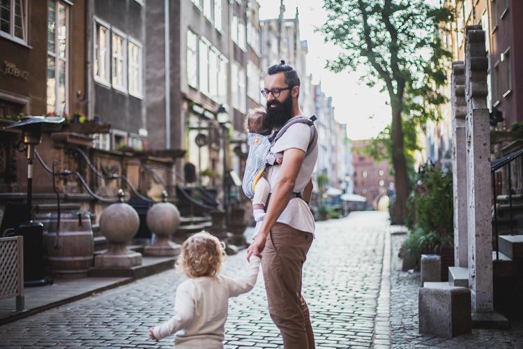 brodaty tata spacerujący po uliczkach Starego Miasta z synem i małą córką w nosidełku