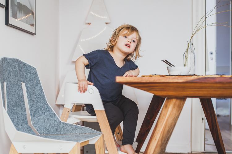 chłopiec siedzi przy drewnianym olejowanym stole z palisandru