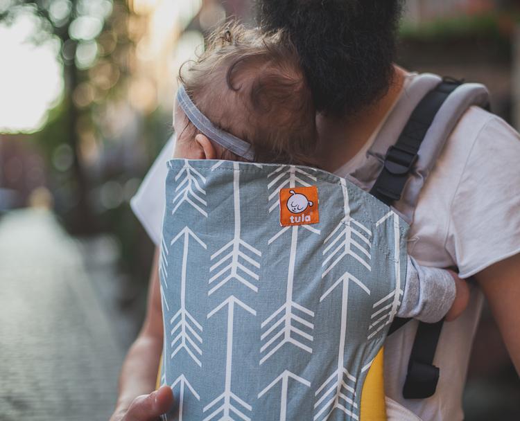 brodaty tata spacerujący po uliczkach Starego Miasta z córką w nosidełku