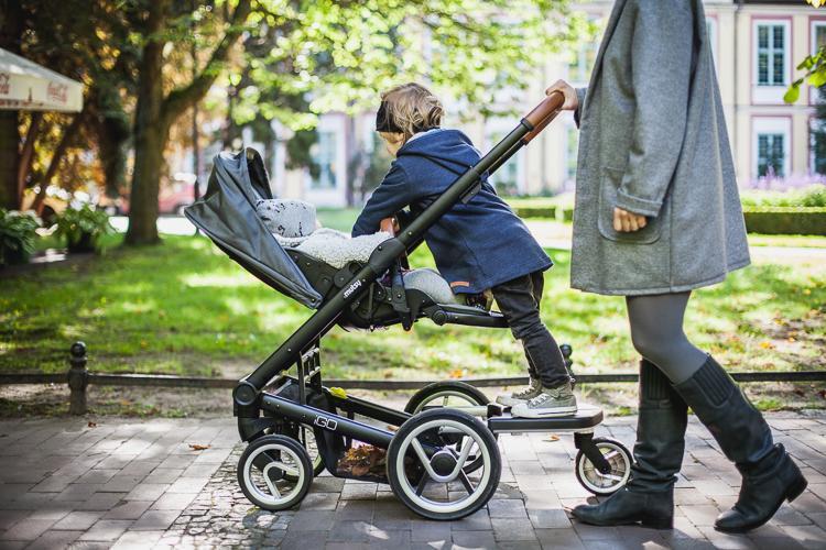 starszy brat jadący na dostawce wózka zajmuje się malutką siostrą leżącą w wózku zpacerowym