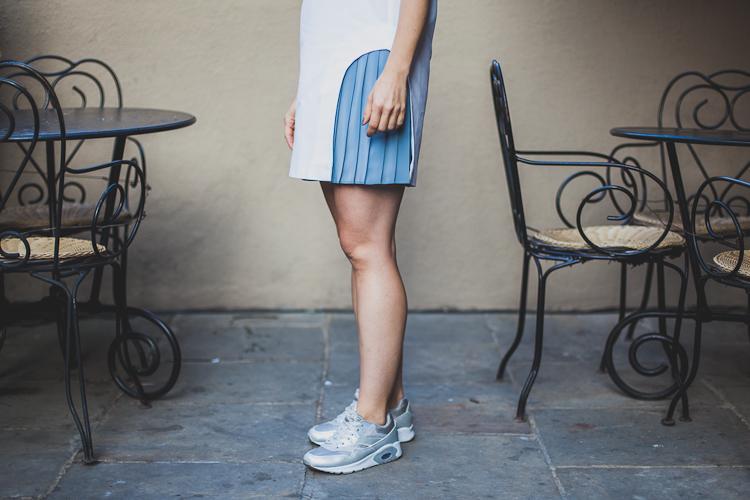 dziewczyna w białej sukience obserwuje ulicę Mariacką z przedproża kawiarni