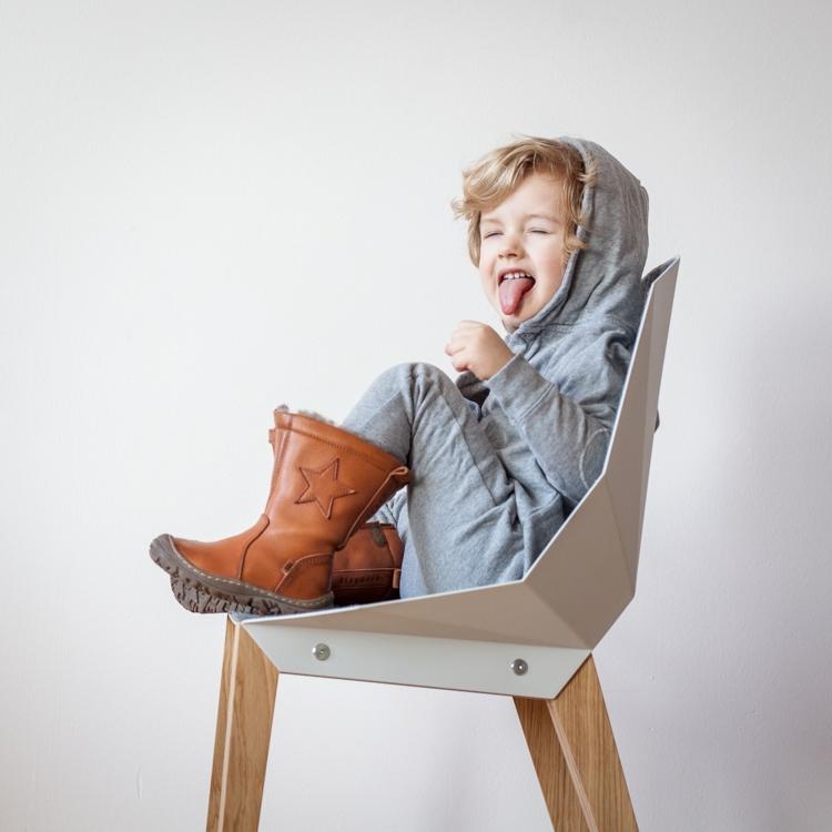 mały chłopiec w rampersie bawi się na w domu