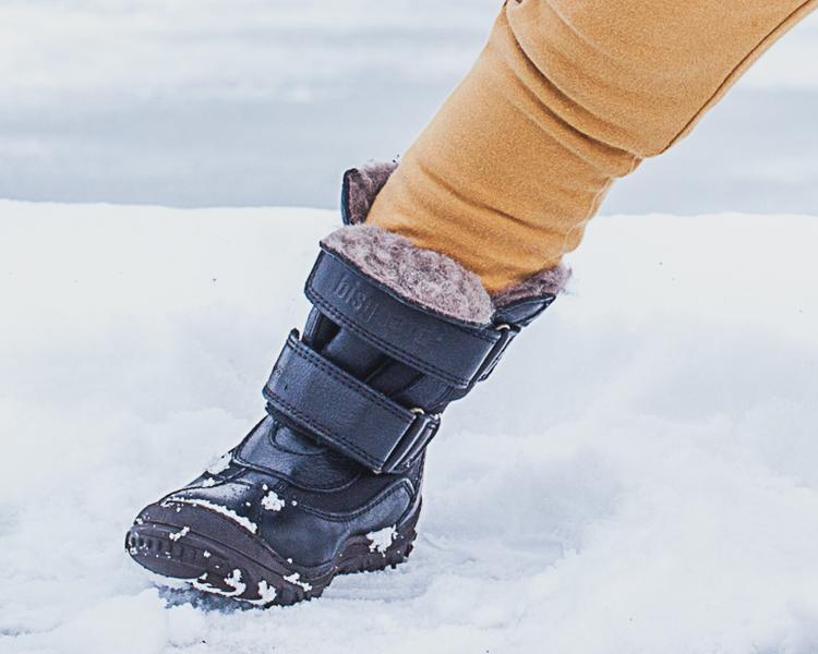 chłopiec w spodniach mon chou i czarnych kozakach bisgaard stoi na zaśnieżonym murku