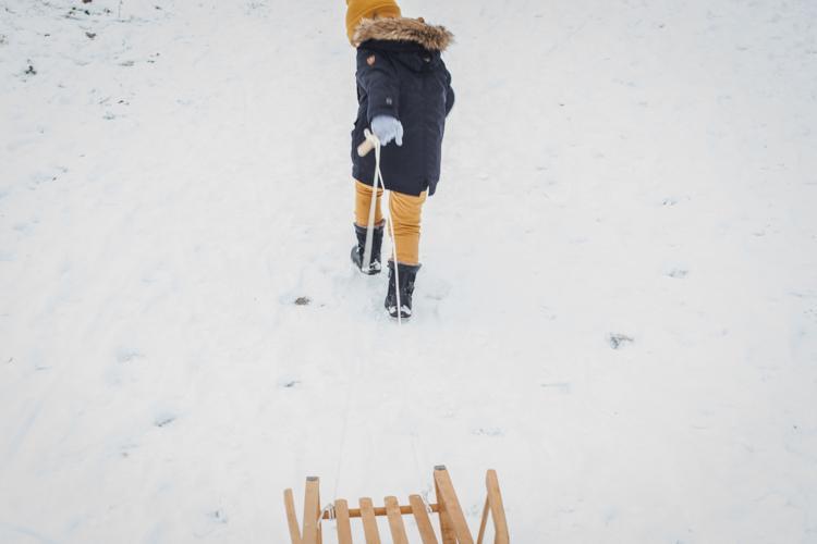 chłopiec w czarnych kozakach bisgaard ciągnie po śniegu zanki