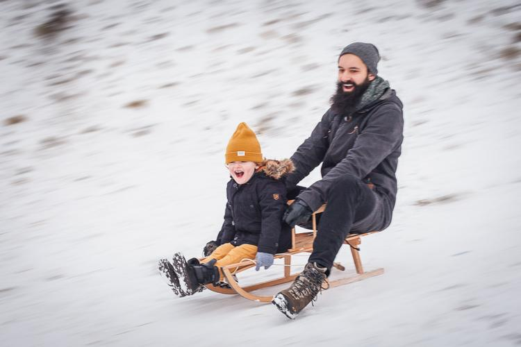 roześmiany brodaty hipster zjeżdża z zaśnieżonej górki z synkiem na sankach