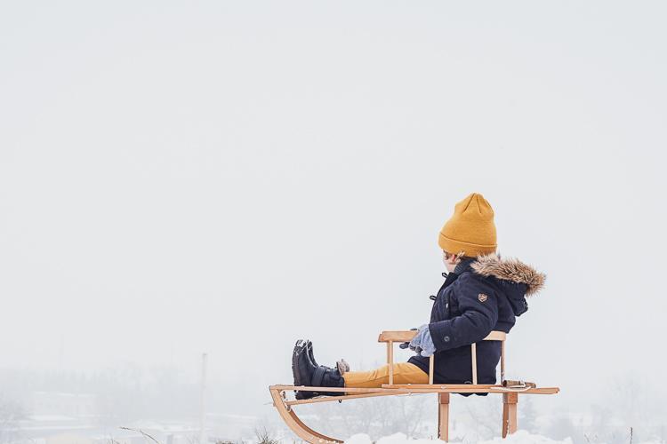 mały chłopiec w czarnych kozakach bisgaard siedzi na szczycie zaśnieżonego stoku na sankach i podziwia widoki