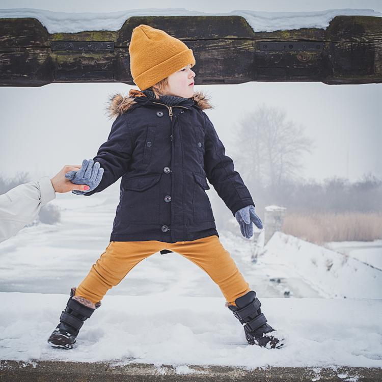 chłopiec w spodniach mon chou i butach bisgaard stoi na zaśnieżonym murku