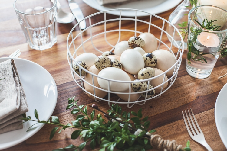 drewniany stół udekorowany na wielkanoc wiązkami z bukszpanu, bazi i rozmarynu