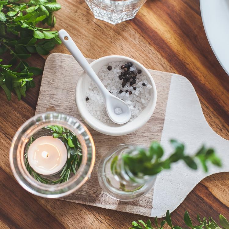 sól i pieprz w ozdobnej miseczce stojącej na drewnianej desce do krojenia
