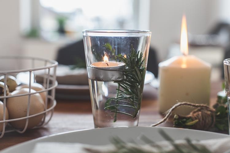 dekoracja wielkanocnego stołu w stylu kinfolk z pływającą świeczką i gałązkami bukszpanu i rozmarynu