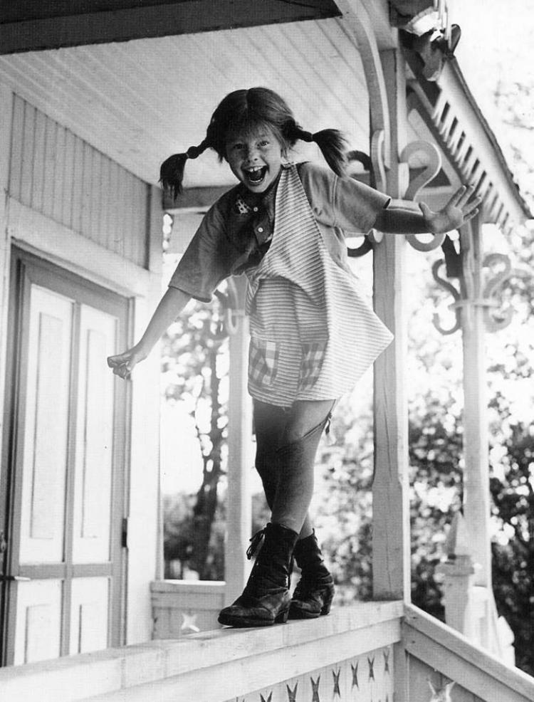 fotografia z filmu o pippi langstrumpf przedstawiająca Pippi idąca po poręczy werandy w letnim drewnianym domku