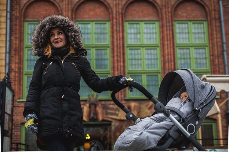 mama w zimowej kurtce spaceruje z małą córeczką w wózku po Gdańskim Długim Pobrzeżu przy rzece Motławie