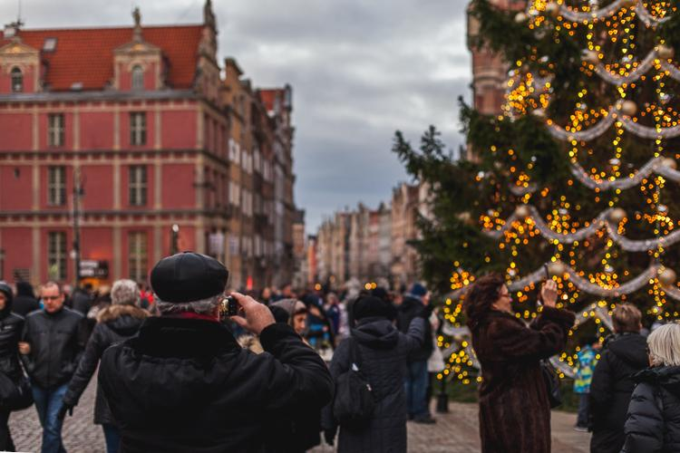 tłum turystów fotografuje się przed choinką oraz świątecznie udekorowanym neptunem na starówce w Gdańsku