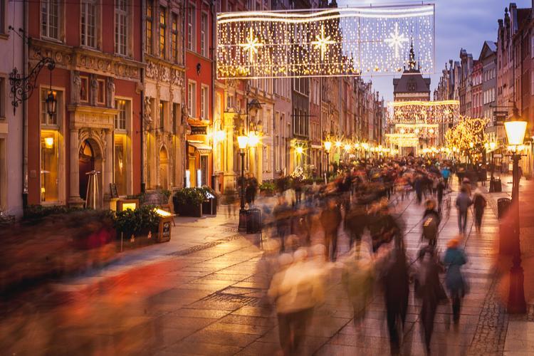 turyści spacerujący wieczorem po rozświetlonej świątecznymi dekoracjami ulicy Długiej w Gdańsku
