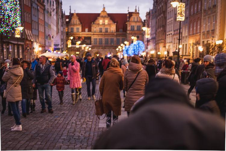 tłum turystów spaceruje po Długim Targu w Gdańsku podziwiając świąteczną atmosferę  oraz choinkę