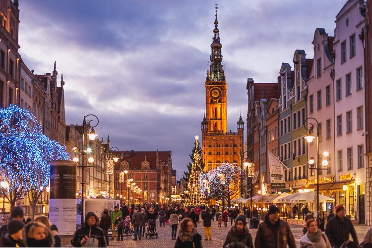 tłum turystów spaceruje po Długim Targu w Gdańsku podziwiając rozświetloną choinkę oraz podświetlony ratusz Głównego Miasta