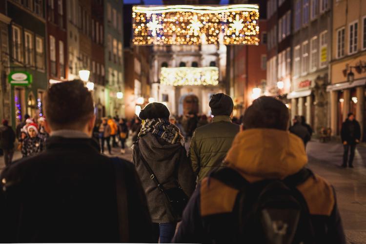 przechodnie podziwiają światełka dekorujące kamienice przy ulicy Długiej w Gdańsku
