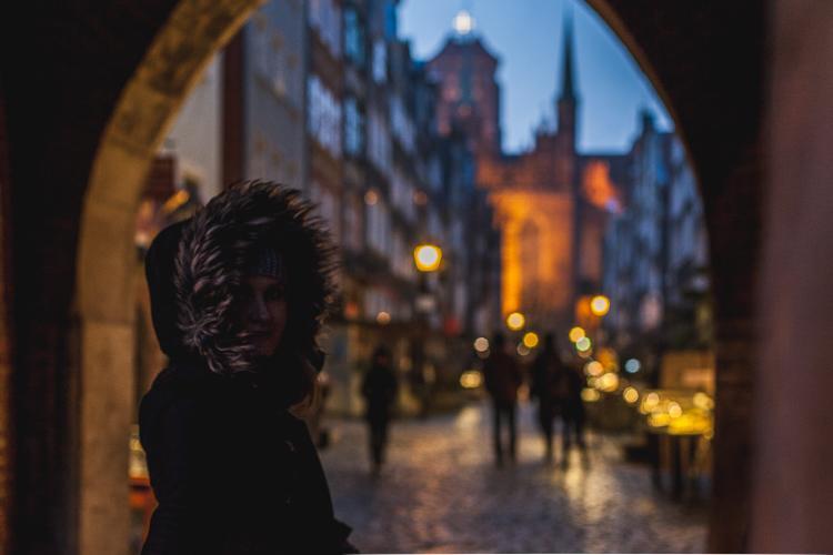 postać kobiety stojąca w bramie Mariackiej w Gdańsku przygląda się wieczornej ulicy Mariackiej