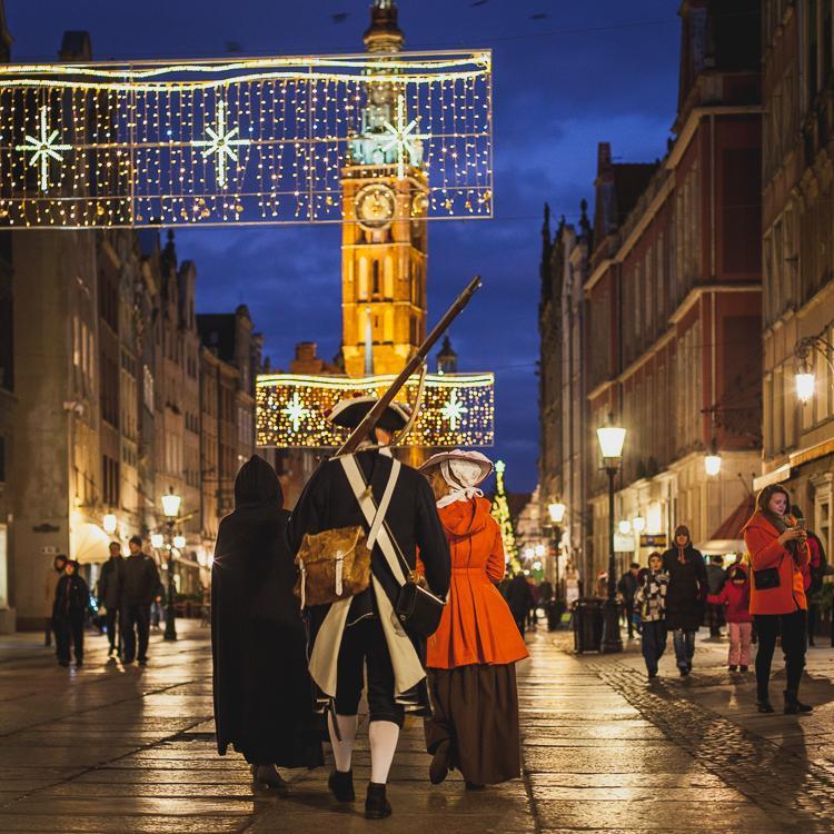 postacie w strojach z XVIIIw. spacerują po wieczornych, rozświetloncyh dekoracjami świątecznymi uliczkach Głównego Miasta w Gdańsku, w tle oświetlona wieża Ratusza