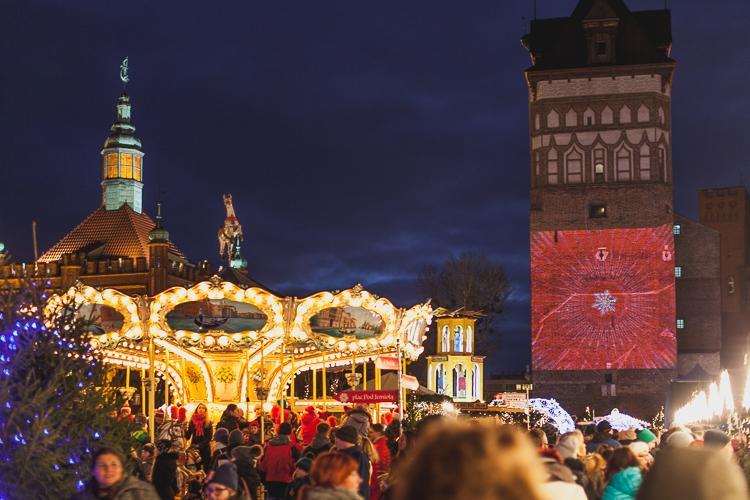 rozśwetlony, magiczny bożonarodzeniowy jarmark z tłumem owiedzających rozstawiony przy Katowni na Targu Węglowym w Gdańsku