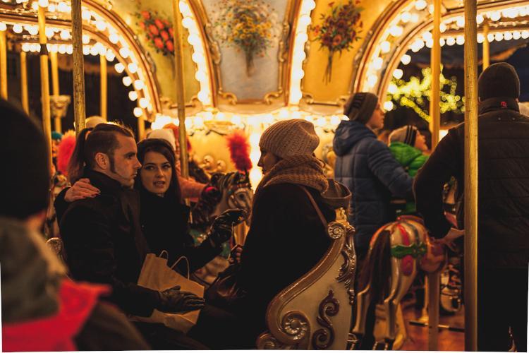 rozbawieni turyści jadący na karuzeli jarmarku bożonarodzeniowego na Targu Węglowym w Gdańsku