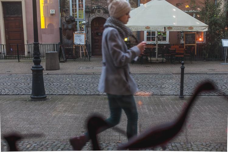 spacerująca po brukowanej uliczce dziewczyna ubrana w szary płaszczyk i wełnianą czapkę