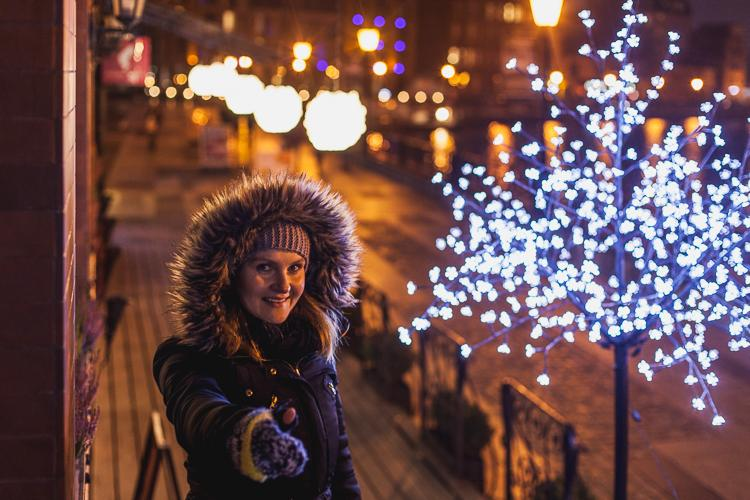 dziewczyna na Długim Pobrzeżu, ubrana w futrzany kaptur zachęca do odwiedzenia Gdańska