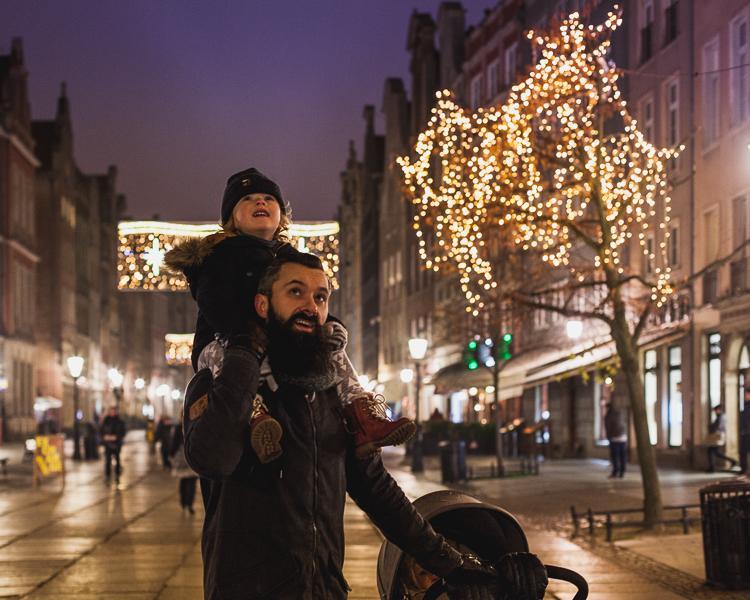 tata niesie synka po świątecznie przystrojonej ulicy Długiej na gdańskiej starówce