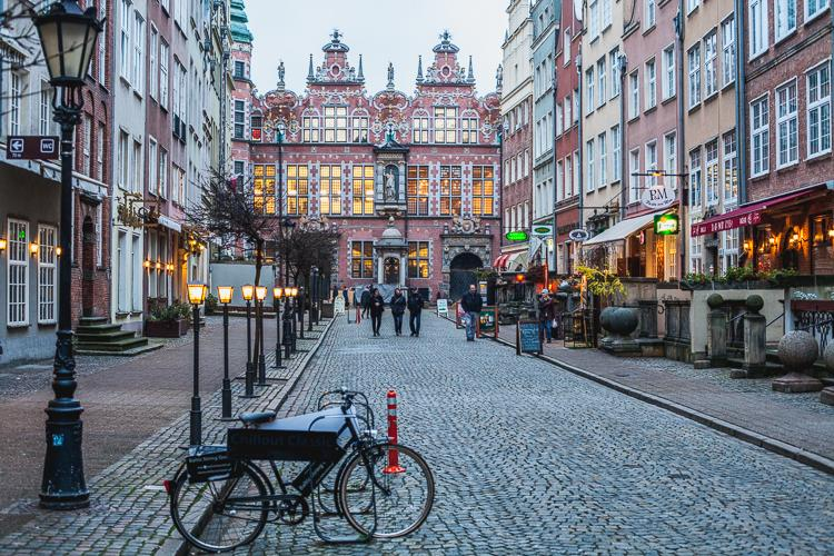 perspektywa odnowionej brukowanej ulicy Piwnej z widokiem na Wieką Zbrojownię w Gdańsku wieczorową porą