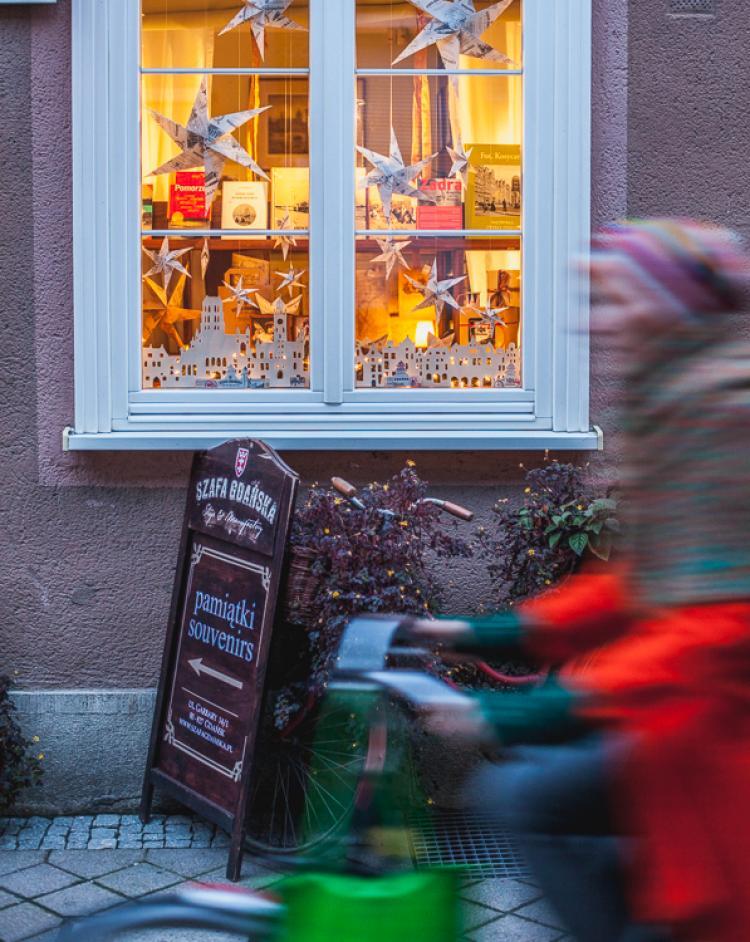 kolorowa rowerzystka przejeżdża przed rozświetloną witryną ze świąteczną dekoracją sklepu przy ulicy Garbary w Gdańsku
